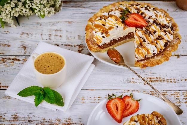 Torta de creme chantilly de sobremesa doce de café da manhã com morango e xícara de café com leite