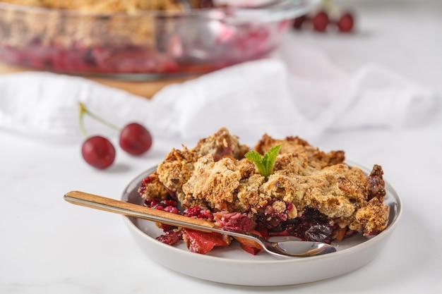 Torta de crumble de frutas vermelhas de verão, superfície clara, café da manhã vegetariano. conceito de comida vegana saudável.