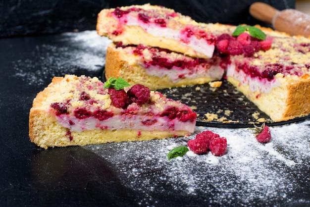 Torta de framboesa com framboesas maduras na culinária caseira com requeijão cortado em pedaços no escuro