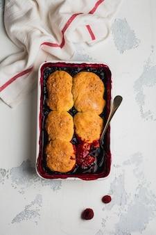 Torta de framboesas e groselhas com sorvete de framboesa na assadeira. bolos de torta de frutas caseiros. fundo cinza vintage. vista do topo.