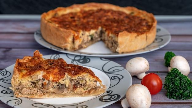 Torta de frango e cogumelos cortada em pedaços perto de tomates cogumelos brócolis