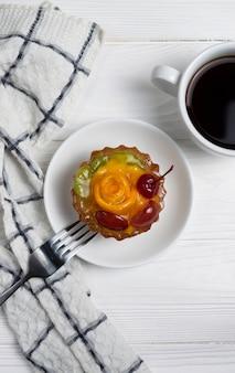 Torta de frutas decorada com cereja laranja e kiwi com café preto na mesa branca