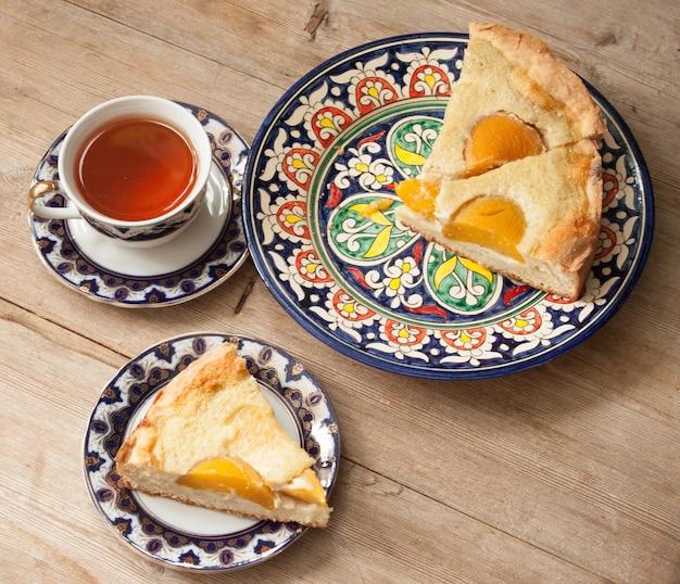 Torta de frutas e pêssego em um pires brilhante com uma xícara de chá no fundo da mesa de madeira