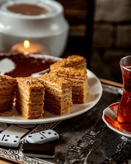 Torta de hidromel cortada em pedaços e um chá preto