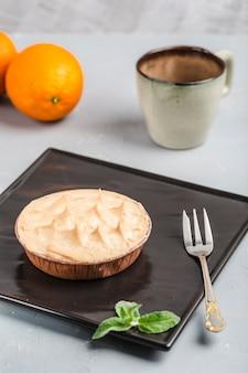 Torta de laranja com uma xícara de café sobre um fundo claro