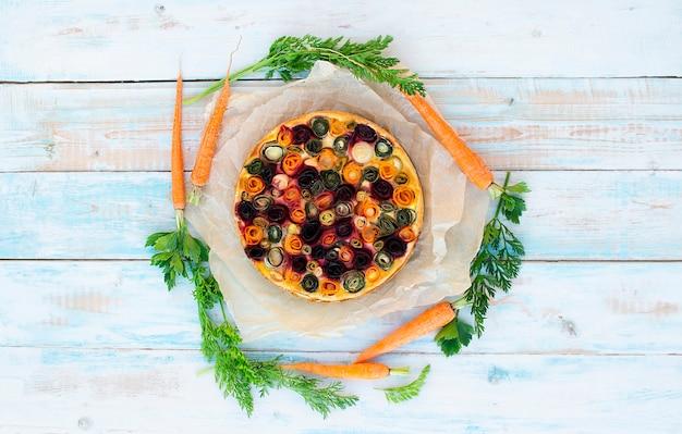 Torta de legumes com cenoura, abobrinha, alho-poró, beterraba e cebolinha. à base de massa de queijo e requeijão. cenouras jovens estão localizadas ao redor. sobre um fundo de madeira. conceito de comida saudável, dieta