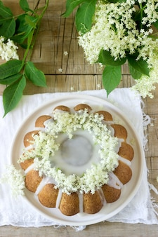 Torta de limão com cobertura de açúcar e xarope de sabugueiro, decorada com flores de sabugueiro. estilo rústico.