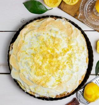 Torta de limão com merengue em um fundo de madeira.