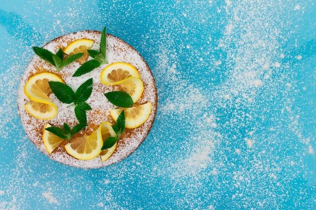Torta de limão com rodelas de limão, hortelã e açúcar de confeiteiro em um fundo azul. vista do topo. copie o espaço.