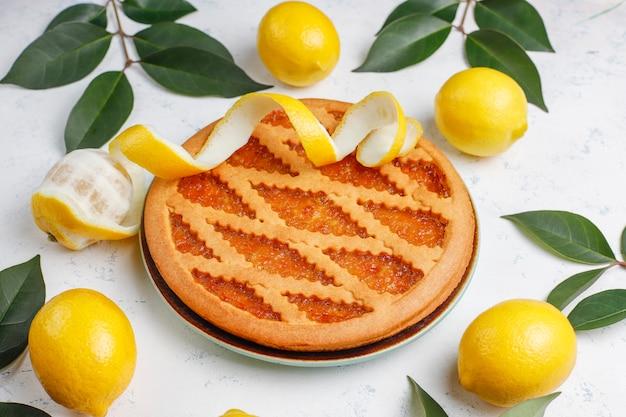 Torta de limão delicioso com limões frescos na luz
