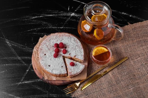 Torta de limão e bebida na travessa de madeira.