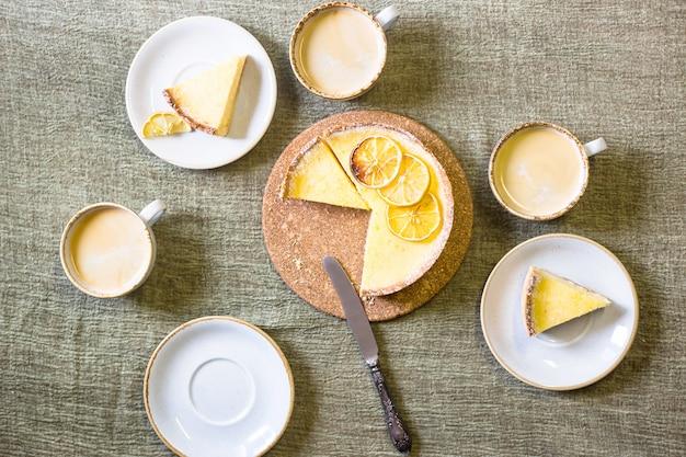 Torta de limão na mesa entre pires e xícaras de café.