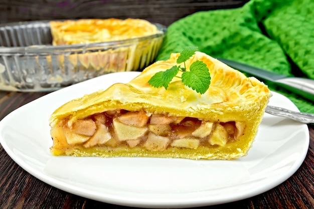 Torta de maçã americana clássica com folhas de hortelã em um prato, um guardanapo, uma torta em forma de vidro sobre um fundo de tábuas de madeira