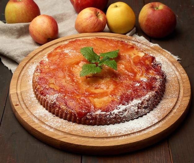 Torta de maçã assada na mesa de madeira e maçãs frescas, mesa de madeira marrom