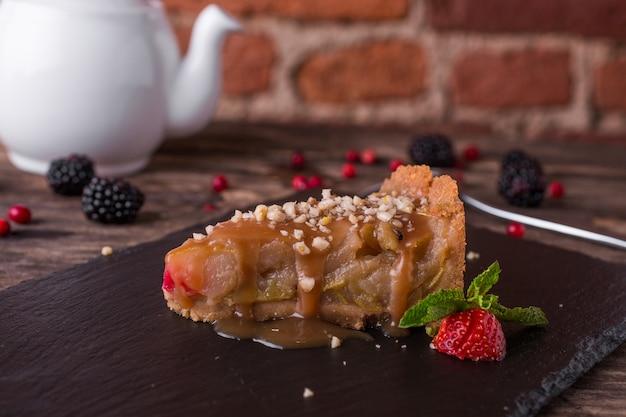 Torta de maçã caramelo num prato de pedra na mesa de madeira rústica