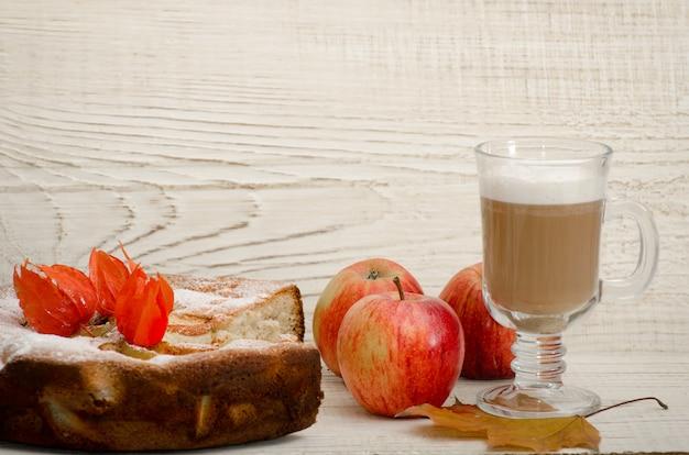 Torta de maçã caseira, cappuccino e maçãs maduras