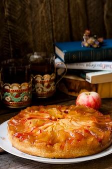 Torta de maçã caseira com canela e caramelo em fundo de madeira