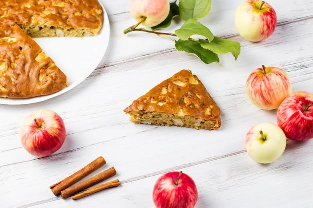 Torta de maçã caseira com canela e maçãs maduras frescas na mesa