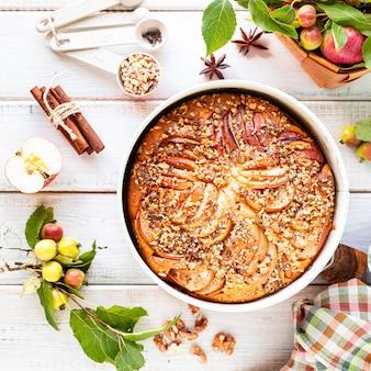 Torta de maçã caseira e ingredientes em um fundo branco de madeira. vista do topo.