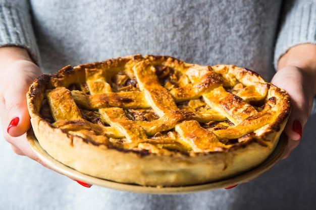 Torta de maçã caseira em mãos femininas