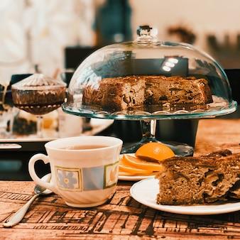 Torta de maçã caseira em um suporte de vidro sobre a mesa uma xícara de chá, um limão, uma colher e um pedaço de bolo cortado.