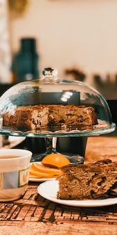 Torta de maçã caseira em um suporte de vidro sobre a mesa uma xícara de chá, um limão, uma colher.