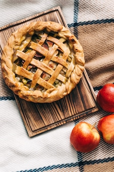 Torta de maçã caseira em uma placa de madeira com canela e uma crosta dourada. estação do outono