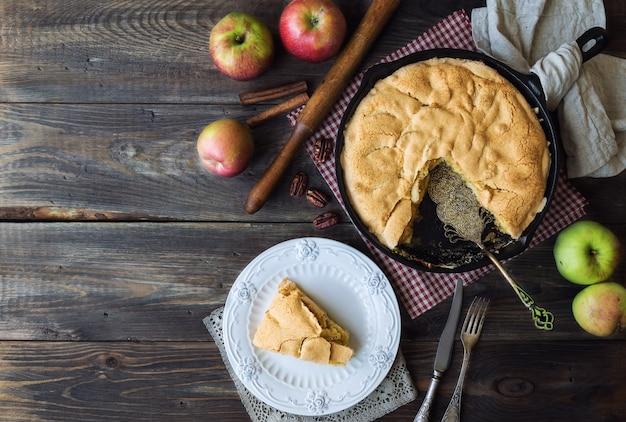 Torta de maçã caseira fresca assada em frigideira de ferro em madeira rústica.