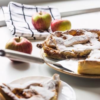 Torta de maçã caseira polvilhada com açúcar em pó com um pedaço fatiado