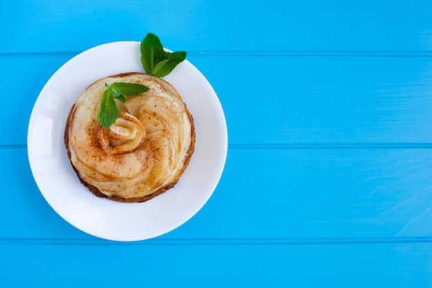 Torta de maçã com canela e hortelã, sobre um fundo azul brilhante de madeira