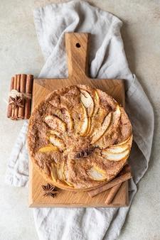 Torta de maçã com canela na placa de madeira, superfície de concreto leve