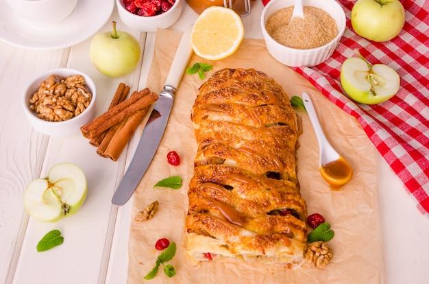 Torta de maçã com cerejas secas, nozes, raspas de limão e canela no fundo branco de madeira