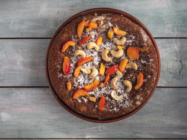 Torta de maçã com fatias de maçã e castanha de caju em um prato marrom vista de cima em um fundo marrom close-up