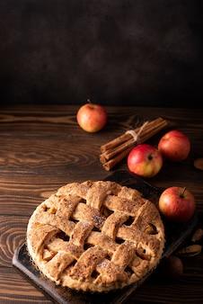 Torta de maçã com maçãs de outono e canela em uma mesa de madeira