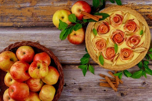 Torta de maçã com maçãs frescas em fundo de madeira.