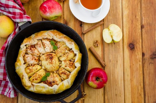 Torta de maçã com massa folhada com canela, nozes e caramelo em uma panela sobre uma mesa de madeira escura