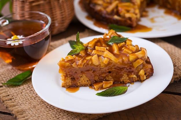 Torta de maçã com molho de caramelo em um fundo de madeira
