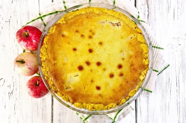 Torta de maçã com molho de creme de leite em uma toalha, frutas em um fundo de prancha de madeira
