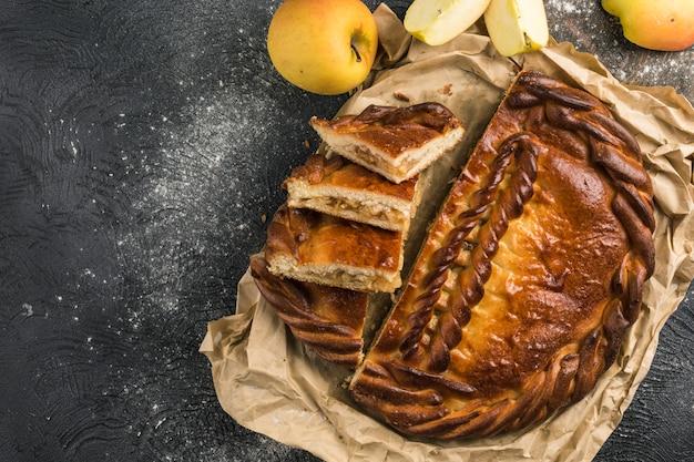 Torta de maçã cortada em pedaços na vista superior do fundo escuro. postura plana.