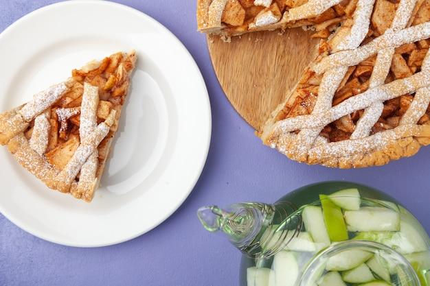 Torta de maçã doce assada caseira charlotte e pedaço de bolo no prato, chá de frutas na panela, espaço de cópia