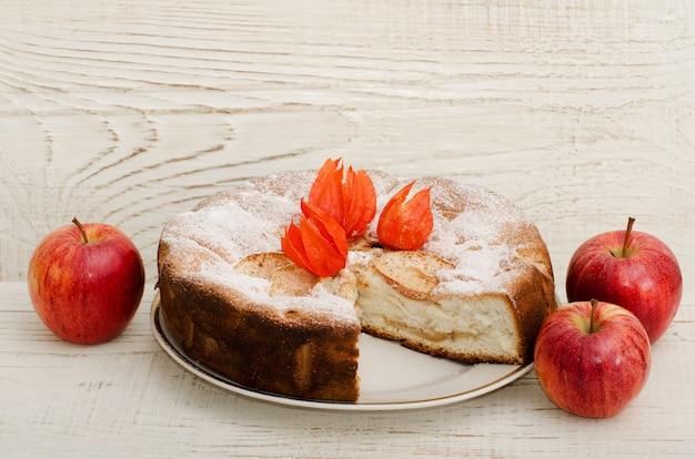 Torta de maçã e maçãs maduras em uma mesa de madeira clara