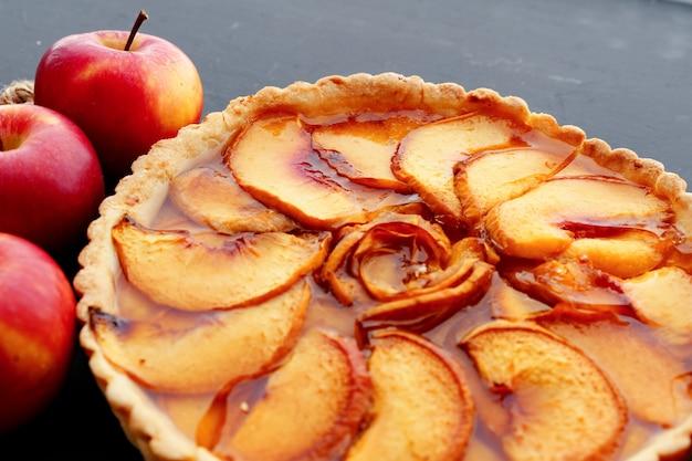 Torta de maçã e maçãs vermelhas na mesa de madeira