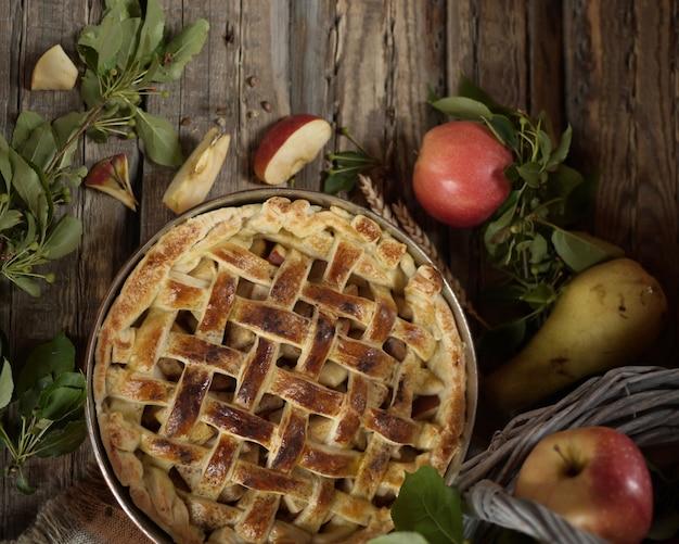 Torta de maçã em forma de cobre. maçãs e flores do campo na cesta velha. estilo rústico. vista do topo