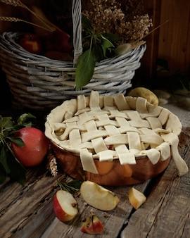 Torta de maçã em forma de cobre. maçãs e flores do campo na cesta velha. estilo rústico