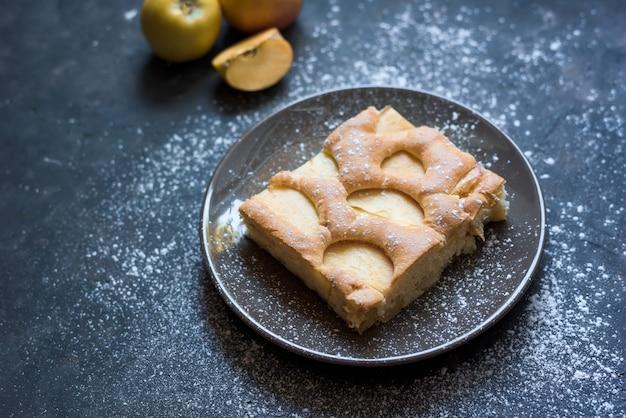 Torta de maçã em um prato marrom em açúcar em pó em um escuro. vista do topo