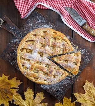 Torta de maçã inteira redonda em uma placa marrom velha retangular