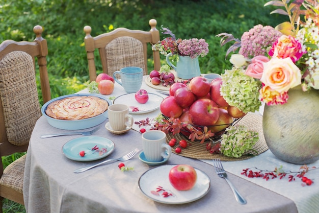Torta de maçã na mesa posta no jardim em dia ensolarado