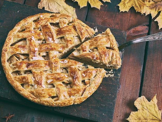 Torta de maçã redonda em uma placa de madeira marrom, massa folhada