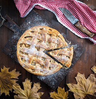 Torta de maçã redonda inteira assada, mesa de madeira, vista superior