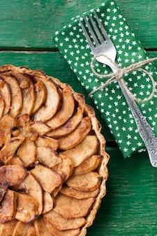 Torta de maçã suculenta com canela e conhaque numa superfície verde